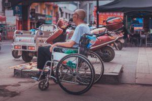 Wheelchair traveler in an Asian country street